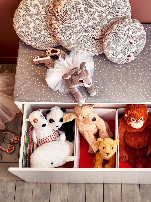 Three NÖJSAM boxes with animal-shaped soft toys sit inside a SMÅSTAD box which has been pulled out from under a bench.