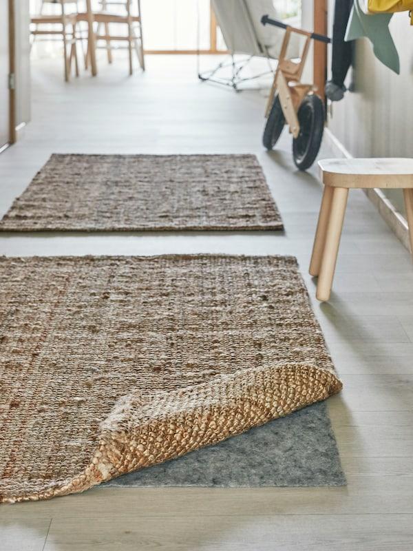 走廊上铺有两张浅棕色的手织地毯,其中一张一角翻起,出于安全考虑,底下贴有防滑垫。