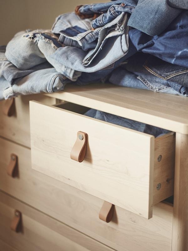 桦木制成的BJÖRKSNÄS 约纳斯 抽屉柜上摆放着一堆牛仔裤。最上面的抽屉打开了一条缝。