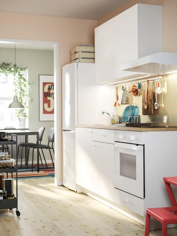 白色的KNOXHULT 诺克胡 厨房,带底柜和壁柜,以及一台冰箱,背景是一个用餐区。