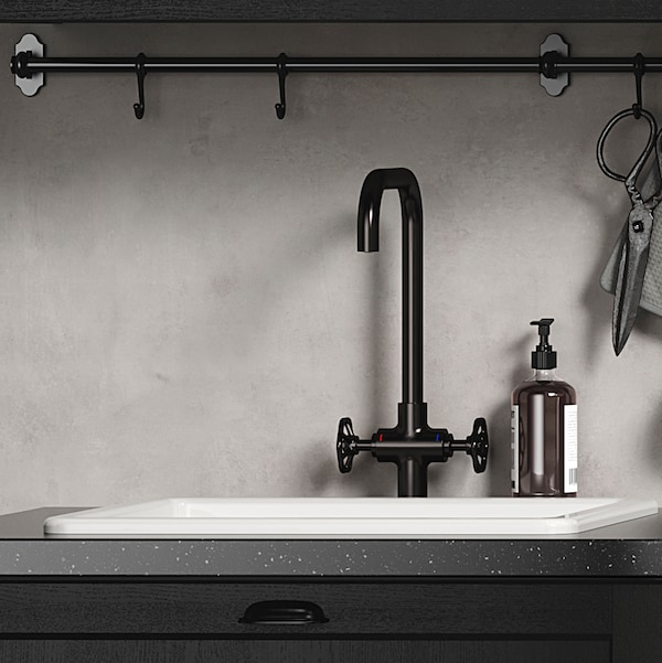 A white kitchen sink and mixer tap in brushed black metal in front of a concrete-effect wall panel.