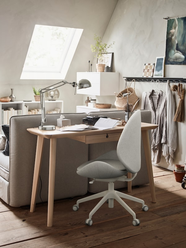 灰色沙发后面、米色HATTEFJÄLL 哈德夫耶尔 办公椅前面放着一张白蜡木贴面LISABO 利萨伯 书桌,桌上摆放着一盏镀镍FORSÅ 芙萨 工作灯。
