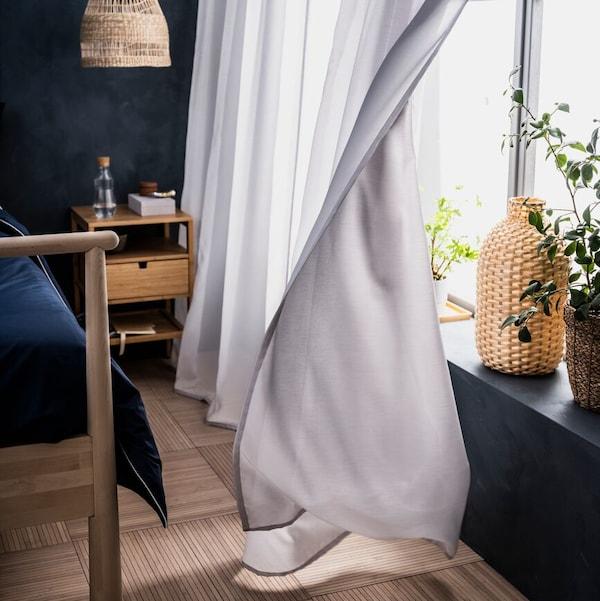 卧室窗户上的GUNRID 古恩里德 空气净化窗帘在微风中飘动着。窗台上有一个KAFFEBÖNA 卡布纳 花瓶。