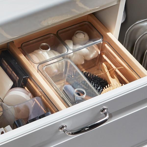 白色脸池架,一个抽屉打开,里面用透明储物盒收纳浴室用品。
