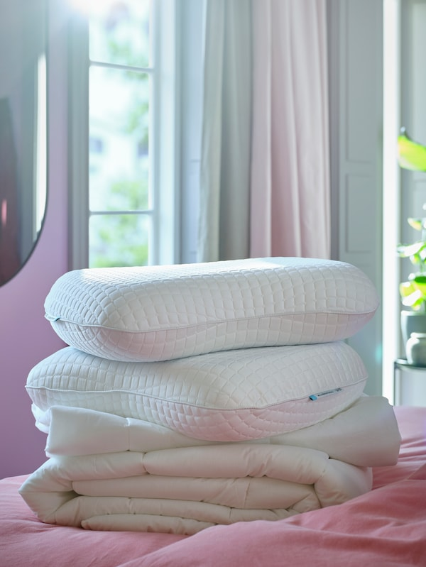 A white quilt and two white KLUBBSPORRE ergonomic pillows sit on a bed with light brown-red ÄNGSLILJA bed linen.