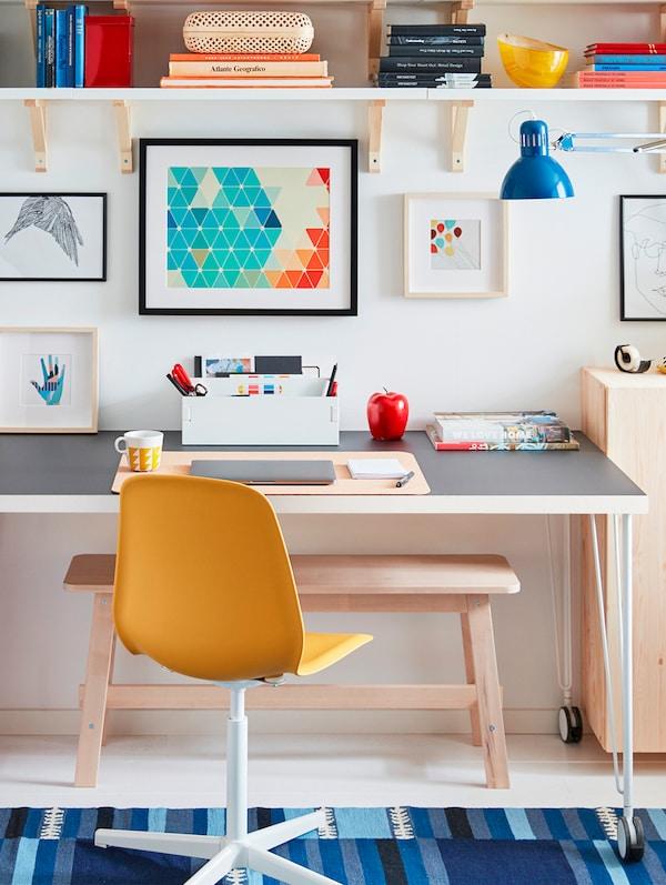 书桌前有一把黄色椅子,桌面摆放着各种各样的书写和学习用品,墙壁上贴着图片,还有一盏蓝色的灯。