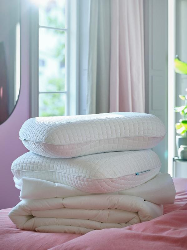 卧室的床上放着羽绒被,羽绒被上是两个KLUBBSPORRE 克鲁布斯珀勒 功能枕头,背景是窗户和窗帘。