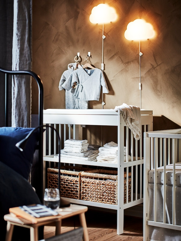 A GULLIVER changing table sits in a bedroom. Two UPPLYST LED wall lamps and some baby clothes hang on the wall behind.