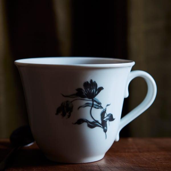 深褐色木桌上放着一只白底蓝花的UPPLAGA 乌普洛卡 杯子。