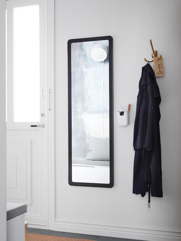 一面GRUA 格鲁瓦 长镜,带黑色镜框,位于白色的门和三头挂钩之间,挂钩上面挂着一件外套。