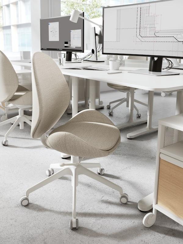 一张白色办公桌前面有一张米黄色转椅,桌面上摆放着一个咖啡杯和电脑屏幕,旁边还有别的办公桌和椅子。