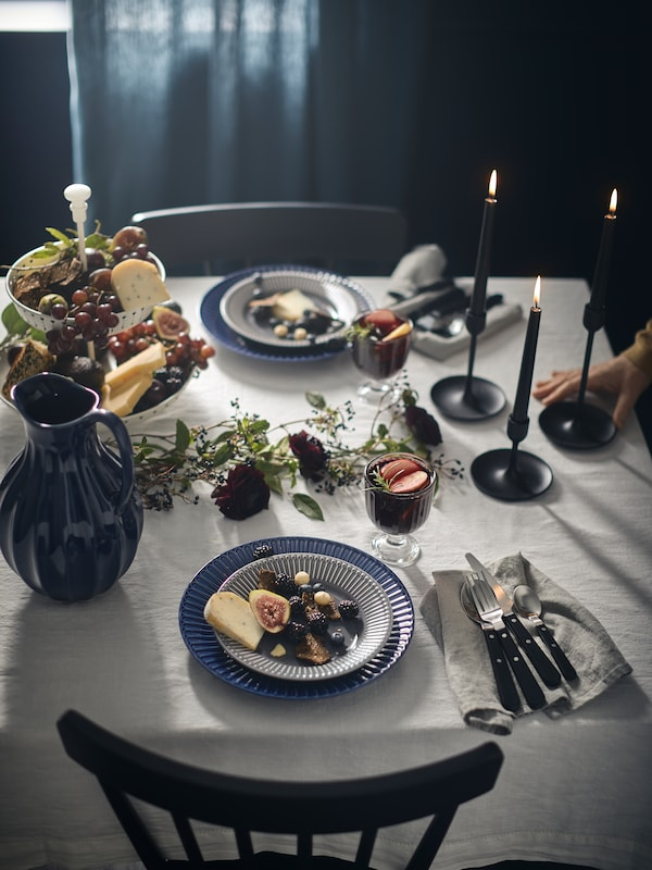 A table is set for a meal with a VANLIGEN vase/jug, STRIMMIG plates holding fruit and cheese, FULLTALIG candlesticks.