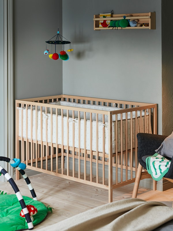 A SNIGLAR cot sits in a corner with a KLAPPA mobile hanging above and near a KLAPPA baby gym sitting on the floor.