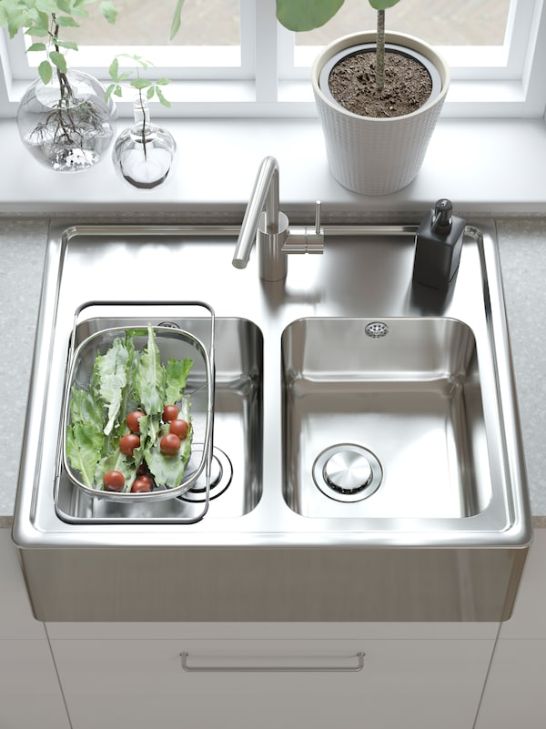 A worktop with an IKEA BREDSJÖN stainless steel kitchen sink with two bowls and a visible front.