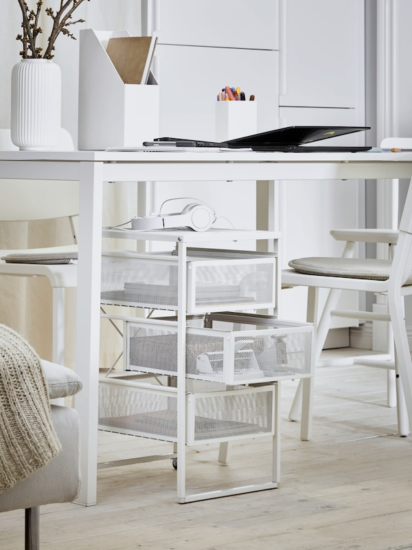 A white desk with diverse items including a computer, file holder and white plant vase, storage underneath and chairs.