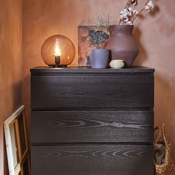 A MALM chest of drawers stands in a corner with a lit FADO table lamp, vases with plants, and other things on top of it.