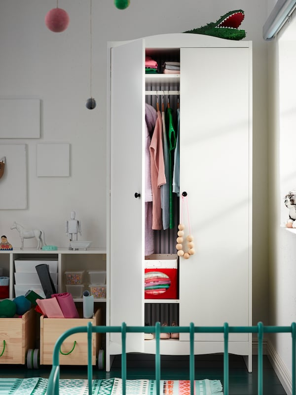 A SMÅGÖRA wardrobe with one door open stands in a corner of a child's room. Colourful clothes are neatly stored inside.