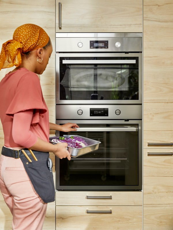 A woman with a head-scarf and a kitchen utility belt, placing a tray of food into an oven, the oven has two levels.