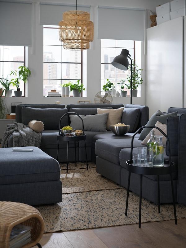 一个单间公寓中摆放了一张大大的VALLENTUNA 瓦伦图 组合沙发和两张黑色BURVIK 伯恩维克 边桌,上面放着饮料和零食。