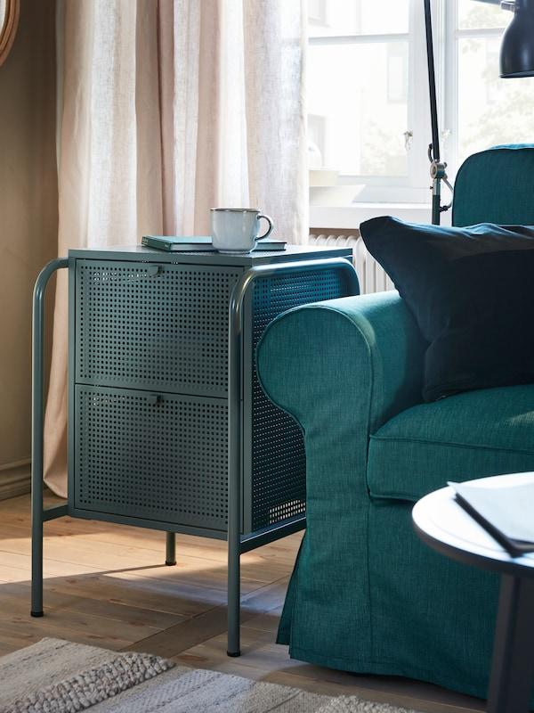 灰绿色的NIKKEBY 尼克比 两斗抽屉柜,上面放着一个GLADELIG 格拉德里 杯子和一本书,旁边是一张深青绿色的EKTORP 爱克托 沙发。