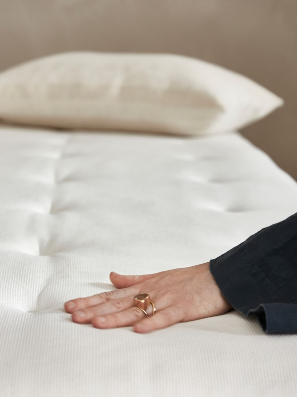 A woman's hand presses down on a HOKKÅSEN pocket spring mattress. There is a pillow lying at the head of the bed.