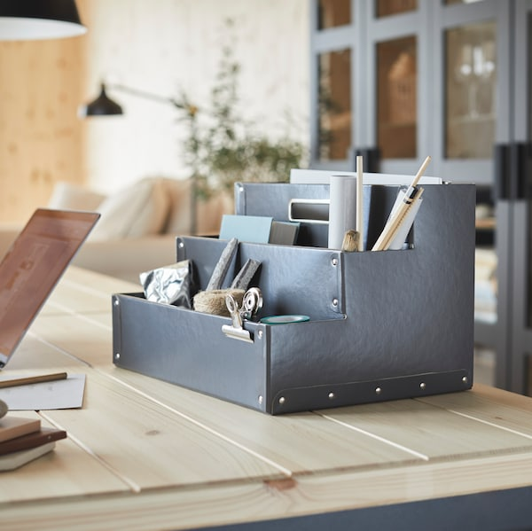 A grey desk organiser holding pencils, small notebooks and other diverse items.