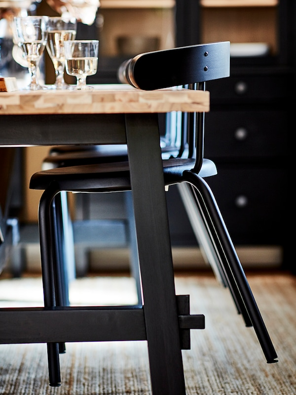 Three anthracite YNGVAR chairs hooked on to a SKOGSTA table by their arms. The table has several filled wine glasses on it.
