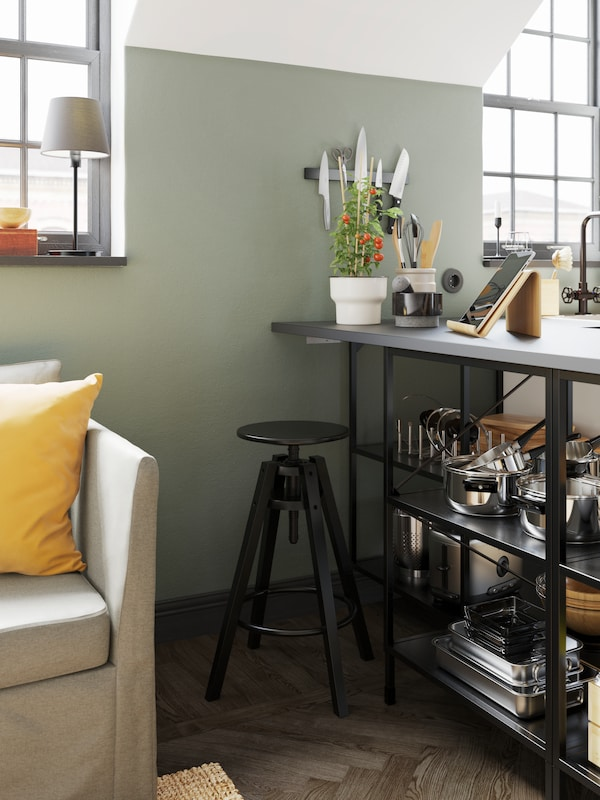 A black bar stool next to open shelves with a grey worktop holding cookware and a tablet stand and plant pot on top.
