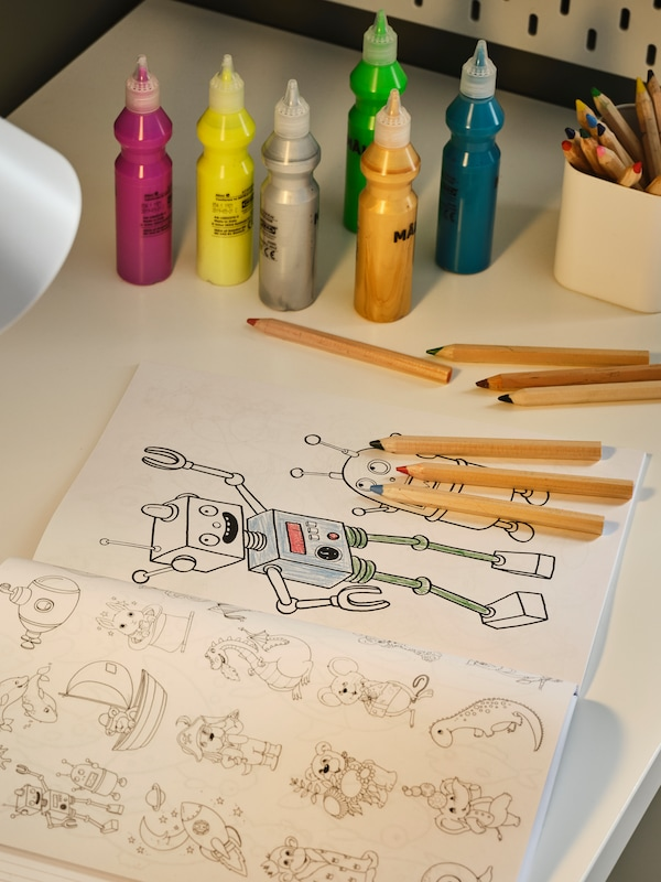 A PÅHL desk with an open colouring book, multicolour MÅLA paints and pencils, and a pot holding pencils on it.