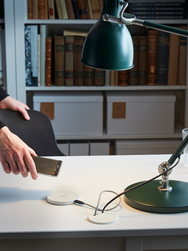 Hand holding a mobile device, by a table with a green work lamp, with shelves behind full of books and boxes.