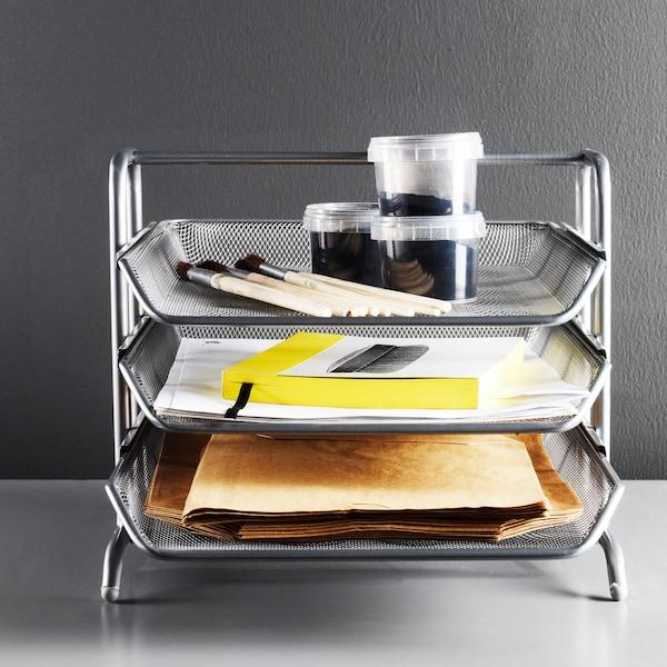 白色桌子上放着金属质感的三层信盘,盛放塑料罐、文件等各式物品。