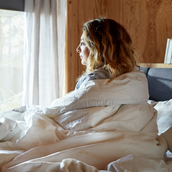 A woman wrapped in a duvet with an ÄNGSLILJA quilt cover sits on a bed looking out of a window with white curtains.
