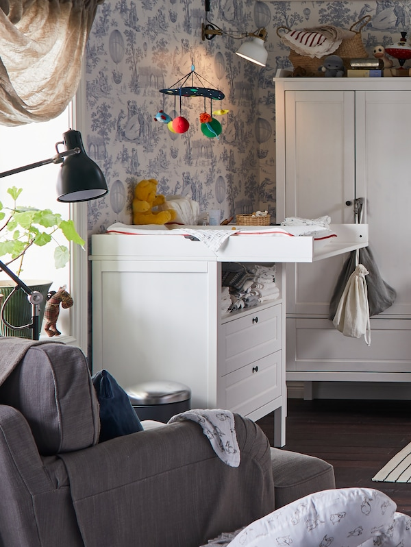 A SUNDVIK changing table/chest of drawers with a KLAPPA mobile hanging above sits near a window in a children's room.