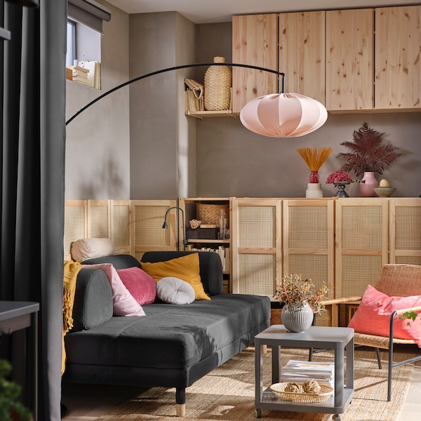 IVAR wall cabinets in a living room containing a dark grey FLOTTEBO sofa-bed with yellow cushions, and a TINGBY side table.