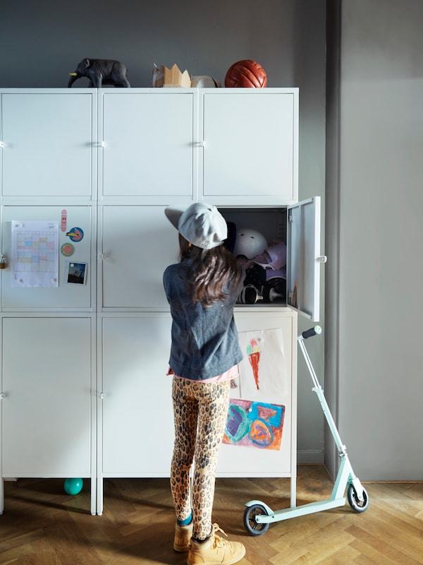戴着鸭舌帽的女孩站在白色储物单元旁边,一扇柜门打开着,里面放着各种各样的物品。她身旁停着一辆轮滑车。