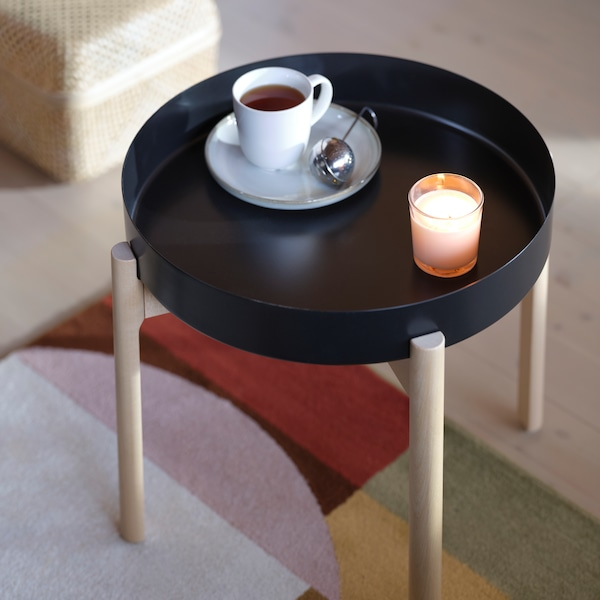 A round, black coffee table, holding a candle and a white coffee cup and saucer on a colourful rug.