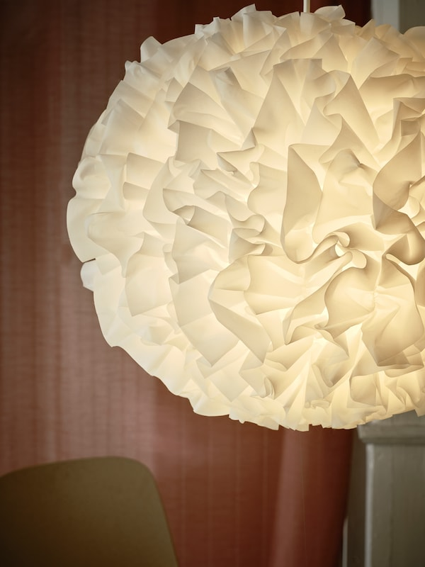A lit VINDKAST pendant lamp made with fluffy white ruffles in a pompom shape, and a pink curtain in the background.