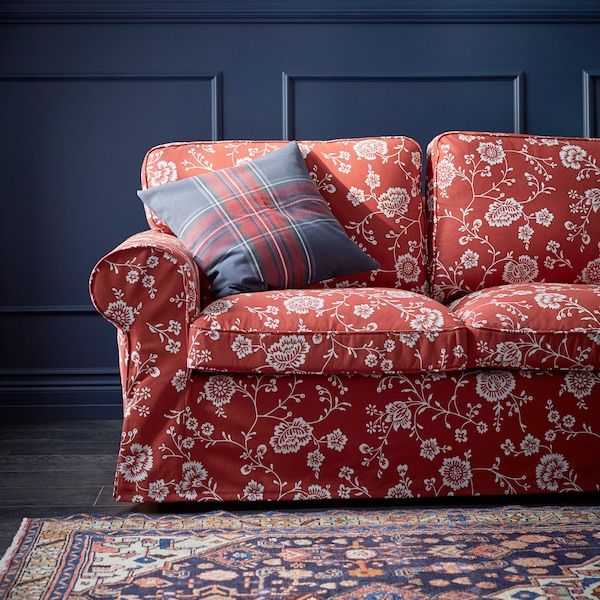 A red sofa with a white floral design on the cover with a cushion, a blue wall behind and a rug on the floor in front.