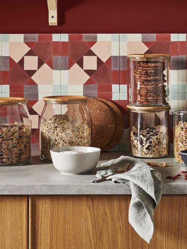 靠墙放着一个灰色的厨房操作台,上面放着IKEA 365+ 罐子,里面装着麦片和饼干,旁边是两个HEAT 席特 锅垫。