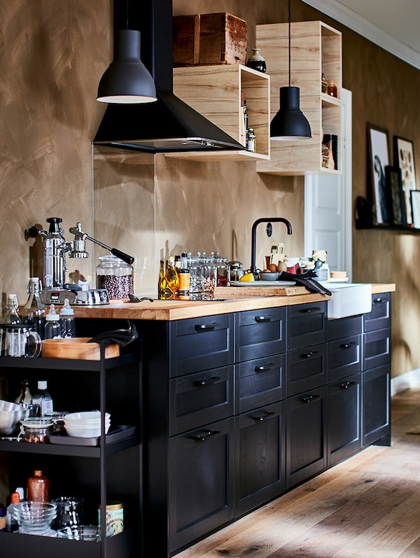 A METOD kitchen with black fronts and drawers, thick wooden worktop, a black trolley with tableware and condiments.