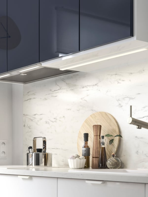 IKEA UNDERVERK kitchen hood is integrated under black-blue cabinets with lit halogen bulbs above a marble effect worktop.