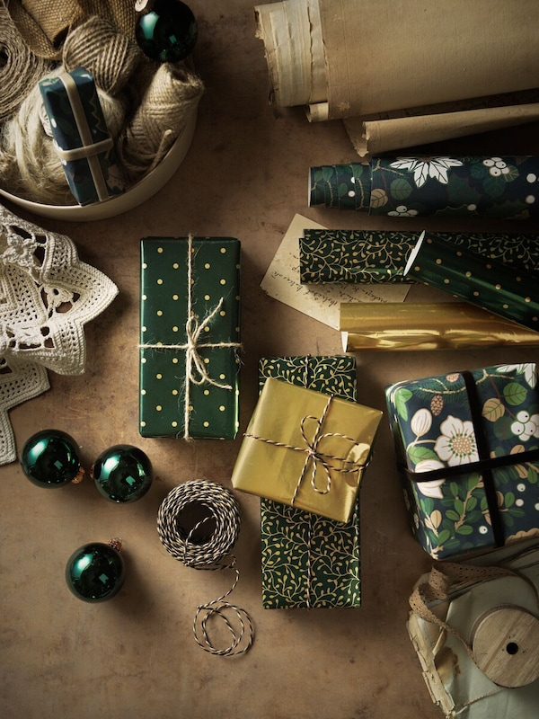 A work surface with lots of wrapped presents, together with wrapping paper, string, ribbon, baubles and other items.