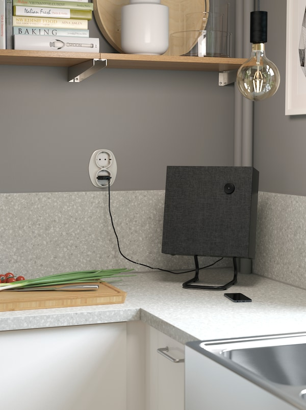 A small square shaped black speaker standing in the corner of a grey worktop next to a chopping board.