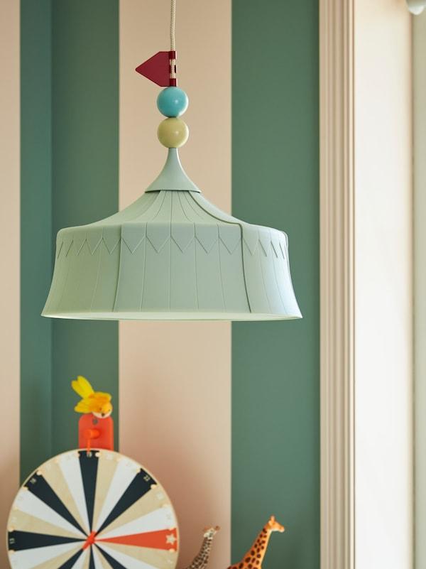 儿童房里悬挂着一盏带有装饰电线的TROLLBO 特洛博 吊灯,下方放着毛绒玩具和幸运轮盘。