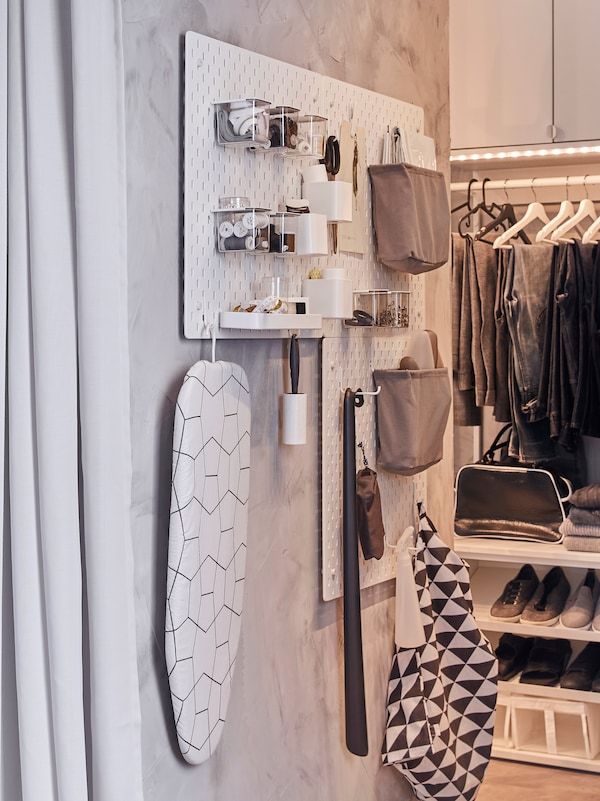 SKÅDIS pegboards and accessories, such as hooks, hang on a narrow wall, where they store and organise clothing care items.