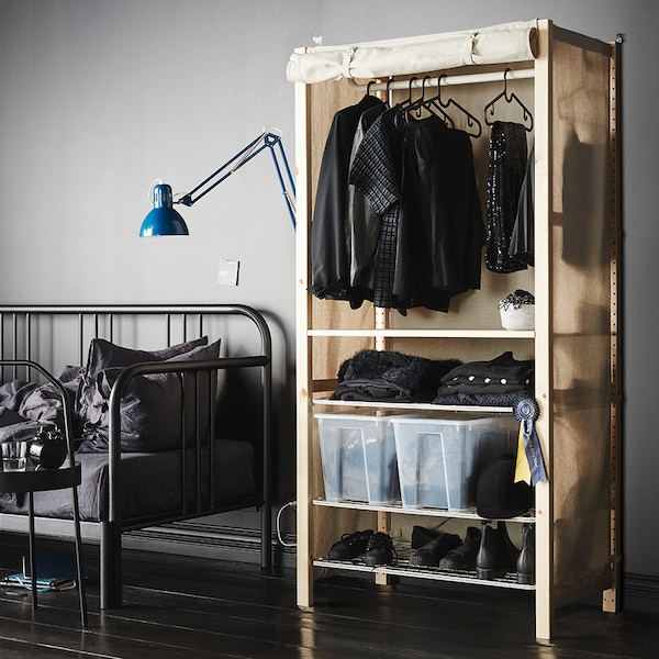 An IVAR shelving unit with rails and a cover filled with clothes, shoes and SAMLA boxes. A FYRESDAL day-bed is beside it.