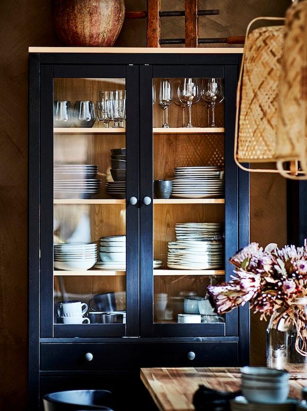 一个带抽屉的HEMNES 汉尼斯 玻璃门柜,里面存放着各种餐具。前面的桌子上方悬挂着两盏KNIXHULT 克尼斯胡特 吊灯。