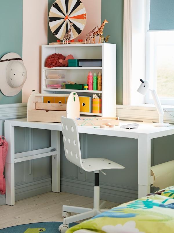 窗前摆放一张白色的PÅHL 佩尔 书桌,上面有一盏KRUX 克鲁克斯 LED工作灯,桌前是一张白色的JULES 尤利斯 儿童书桌椅。
