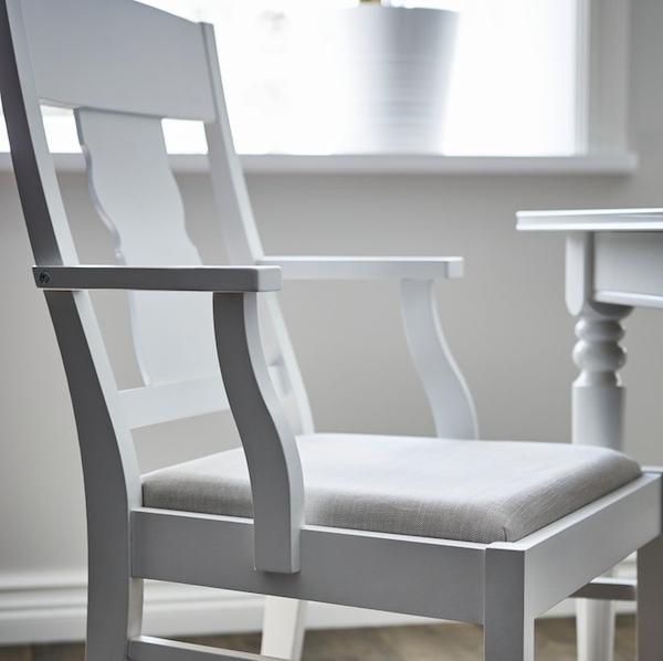 A white INGATORP chair with arm rests and a seat in Nordvalla beige upholstery by a table in a white room by a window.