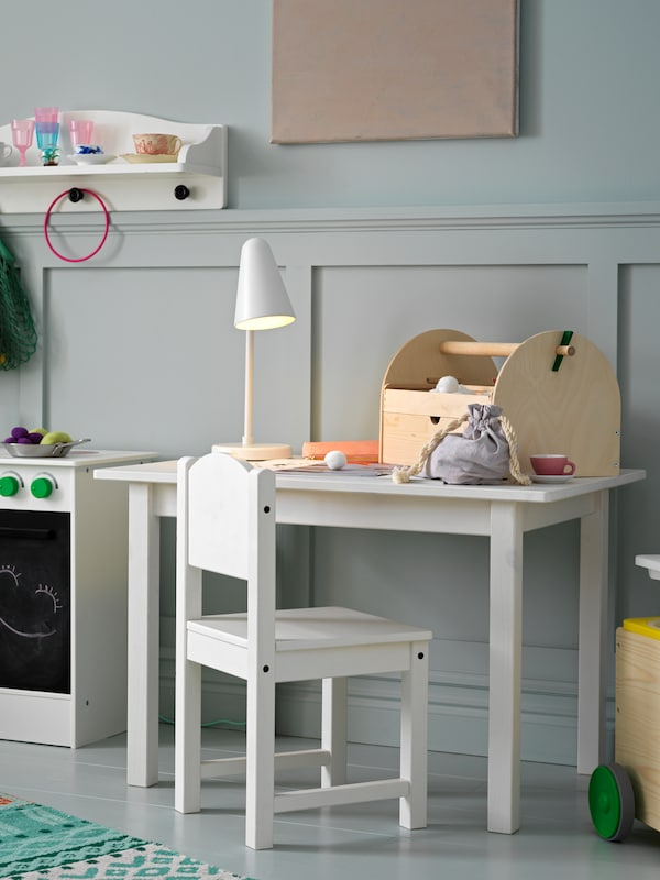 A SUNDVIK children's chair and a SUNDVIK children's table with a FUBBLA LED work lamp on top stand in a child's room.